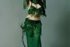Aisha in an emerald green beaded costume.