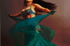 A whirling Aisha Ali in turquoise costume.