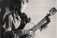 Young Phillip Harland as an ethnomusicologist, playing Spanish guitar.